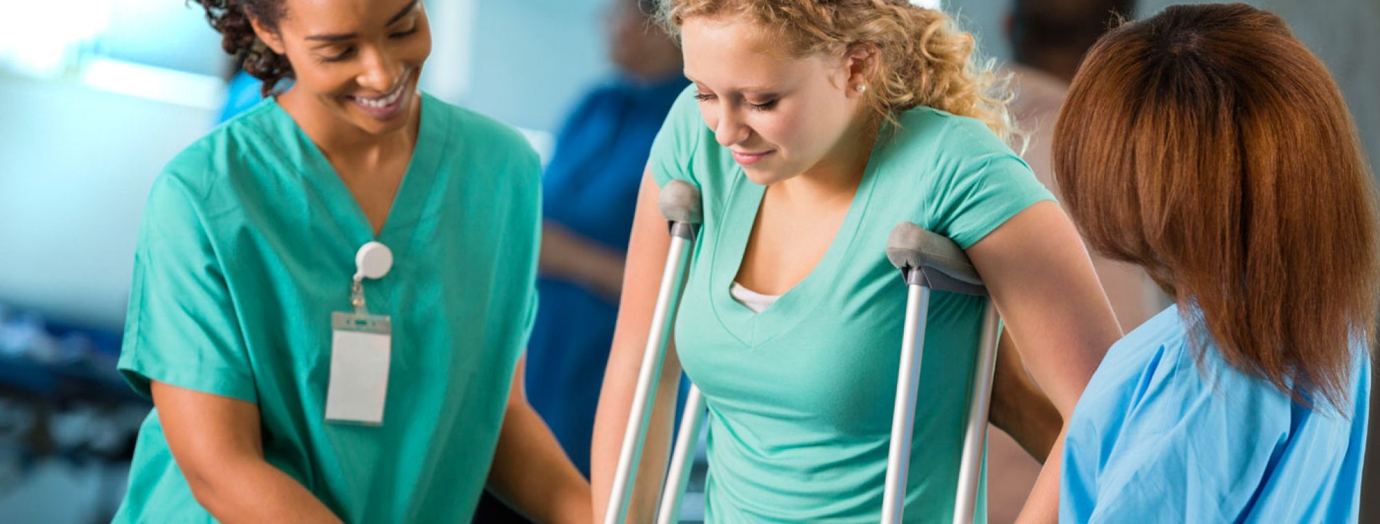 therapy staff helping patient on crutches